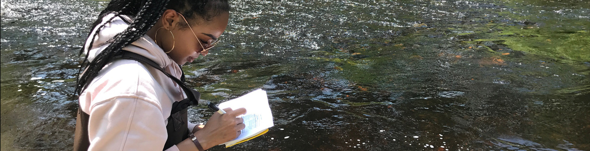 Environmental Science graduate student taking notes in the field