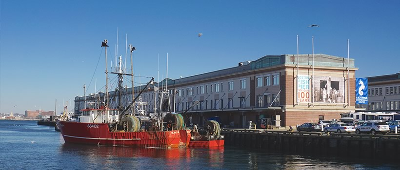 Fishing boat docked at covered pier building in Boston Harbor is on the landing page for UMass Boston's aquaculture program. (photo credit Emily Moothart)