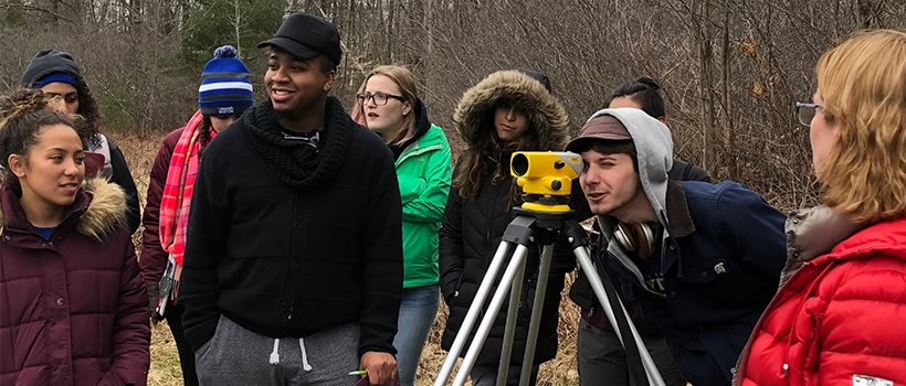 Students look through a surveying viewing device on a tripod outside in wooded area.
