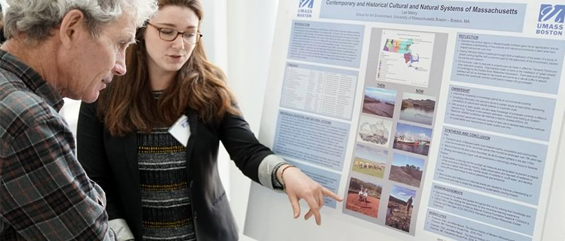 Student shows poster board of her environmental research to a visitor.