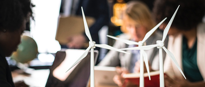 Students work in  a classroom with miniature wind turbines on the table.