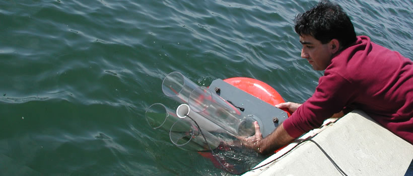 student leans out of a boat to collect water sample near UMass Boston.